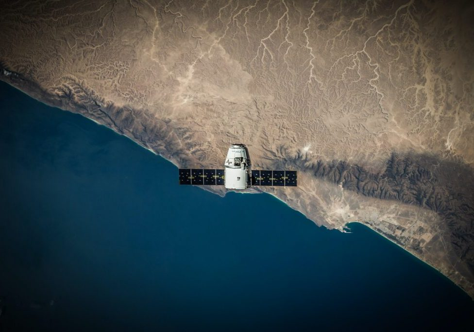 Picture of satellite in the sky above a land coast line
